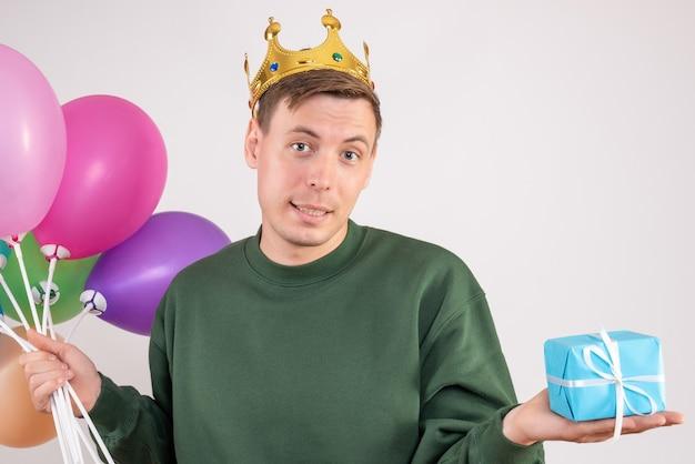 Junger mann, der luftballons und wenig geschenk auf weiß hält