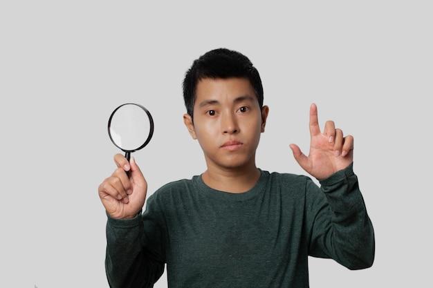 Junger mann, der lupe hält und zeigefinger mit neuer idee auf grauem hintergrund zeigt.
