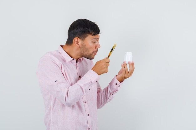 Junger mann, der lupe über pillenflasche in der vorderansicht des rosa hemdes hält.