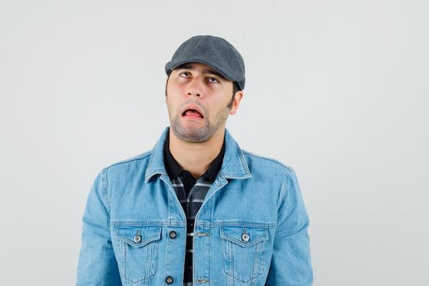 Junger mann, der lustiges gesicht im t-shirt, in der jacke, in der mütze hat und sorglos schaut.