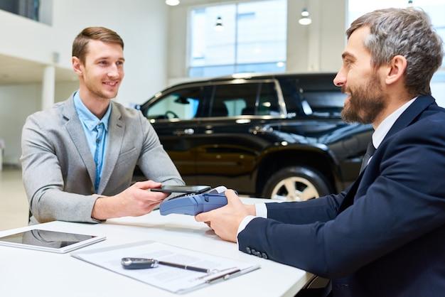 Junger mann, der luxusauto kauft