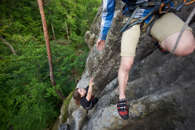 Junger mann, der mädchen hilft, felsigen berggipfel zu klettern.