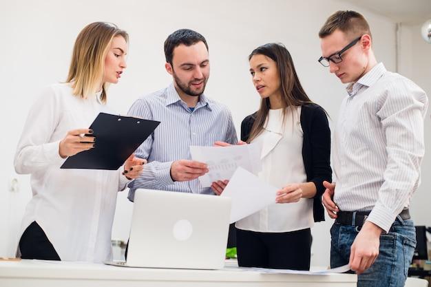 Junger mann, der marktforschung mit kollegen in einem treffen bespricht. team von fachleuten, die konversation im konferenzraum haben dokumente suchen.