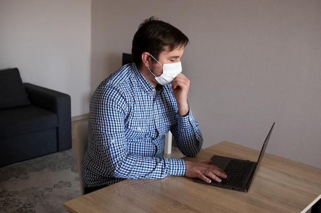 Junger mann, der maske trägt, die an seinem computer von zu hause aus arbeitet, coronavirus, krankheit, infektion, quarantäne, medizinische maske