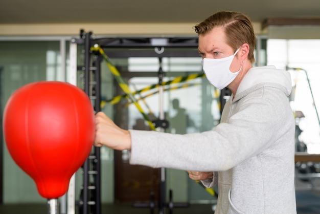 Junger mann, der maske und boxen an der turnhalle trägt