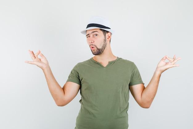 Junger mann, der meditation tut und auge in grünem t-shirt und hut zwinkert