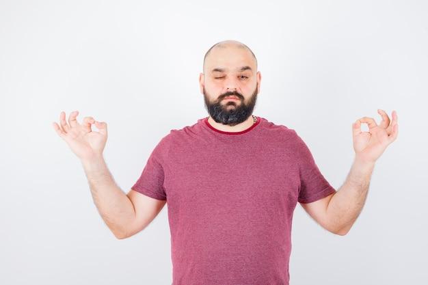 Junger mann, der meditation tut, während er in rosa t-shirt zwinkert und ruhig aussieht. vorderansicht.