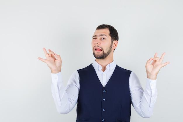 Junger mann, der meditation und augenzwinkern im hemd tut