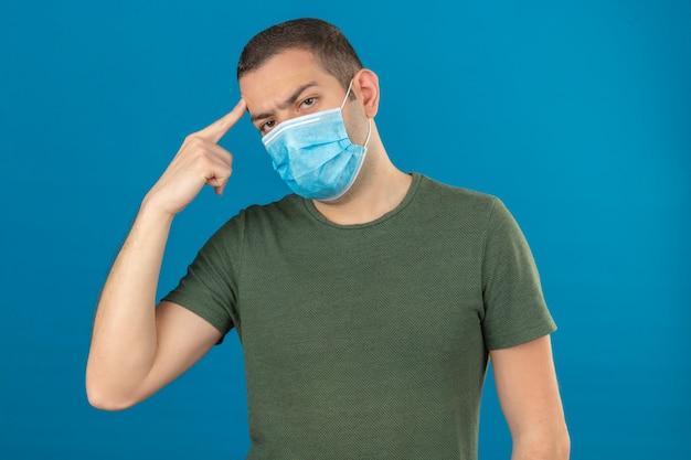 Junger mann, der medizinische gesichtsmaske trägt, die seinen kopf mit dem auf blau lokalisierten finger berührt
