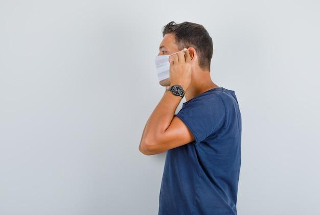 Junger mann, der medizinische maske im dunkelblauen t-shirt trägt.