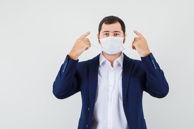 Junger mann, der medizinische maske im hemd abzieht