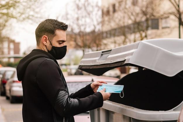 Junger mann, der medizinische maske in den recyclingbehälter wirft. einmalmaske. konzept von coronavirus oder covid-19 und weltumwelttag
