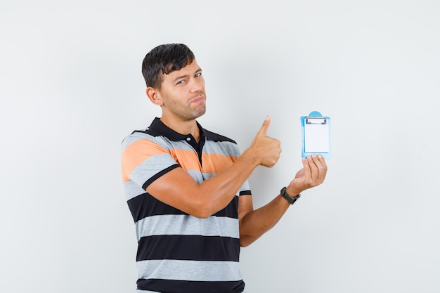 Junger mann, der mini-zwischenablage mit daumen oben in der t-shirt-vorderansicht hält.