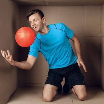 Junger mann, der mit ball in der pappschachtel spielt.