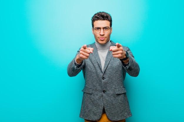 Junger mann, der mit beiden fingern und wütendem gesichtsausdruck auf die kamera zeigt und ihnen sagt, sie sollen ihre pflicht gegen die blaue wand tun