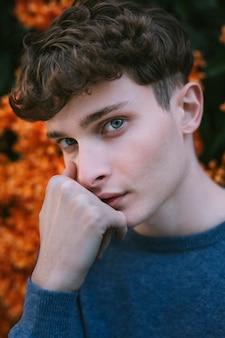 Junger mann, der mit blauen augen anstarrt