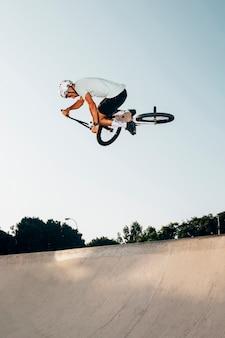 Junger mann, der mit bmx fahrrad springt