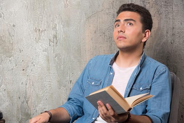 Junger mann, der mit buch oben schaut und auf stuhl sitzt. hochwertiges foto