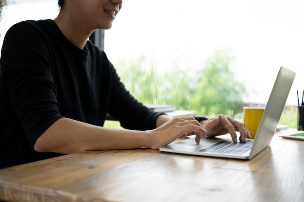 Junger mann, der mit computerlaptop im kreativbüro arbeitet.