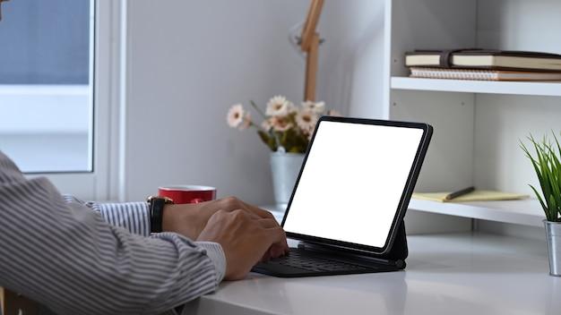 Junger mann, der mit computertablett zu hause büroraum arbeitet