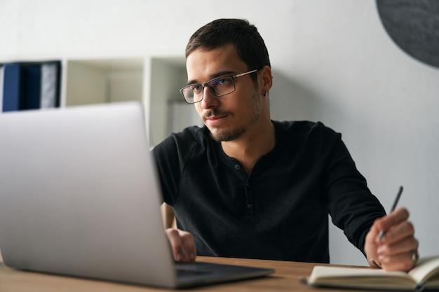Junger mann, der mit computertelefon und tablet am tisch arbeitet, während er kaffee trinkt