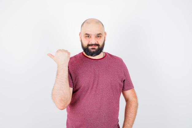 Junger mann, der mit daumen im t-shirt auf die rechte seite zeigt und glücklich aussieht, vorderansicht.