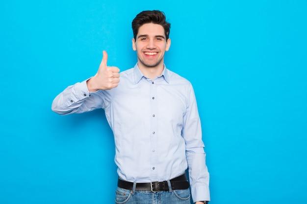 Junger mann, der mit daumen oben auf blauem raum lächelt