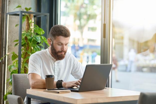 Junger mann, der mit dem laptop sitzt nahe panoramischen fenstern arbeitet.