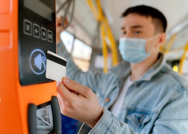 Junger mann, der mit dem stadtbus reist, der mit buskarte zahlt