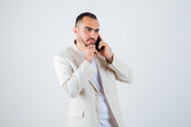 Junger mann, der mit dem telefon spricht und die wange in weißem t-shirt, jacke und konzentriertem blick auf die hand lehnt, vorderansicht.