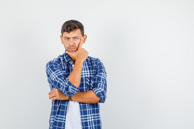 Junger mann, der mit den fingern auf wange und kinn im hemd denkt und düster, vorderansicht schaut.