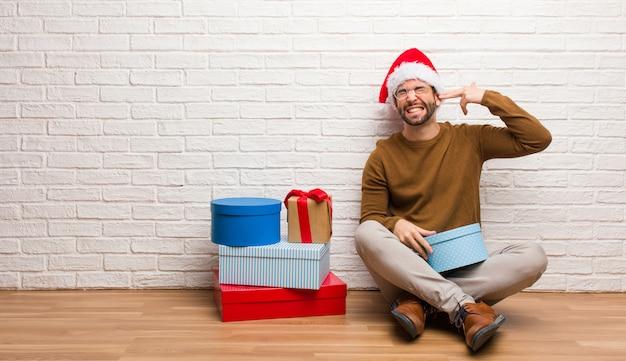 Junger mann, der mit den geschenken feiern das weihnachten tut eine selbstmordgeste sitzt