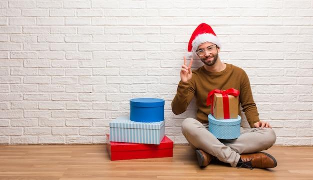 Junger mann, der mit den geschenken feiern das weihnachten zeigt nummer zwei sitzt