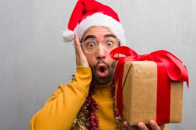 Junger mann, der mit den geschenken feiern weihnachten überrascht und entsetzt sitzt