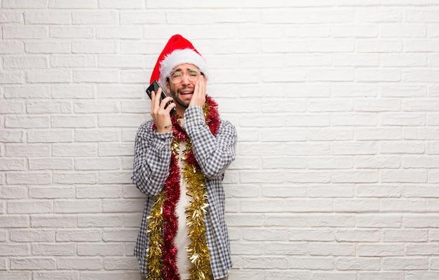 Junger mann, der mit den geschenken feiern weihnachten verzweifelt und traurig sitzt