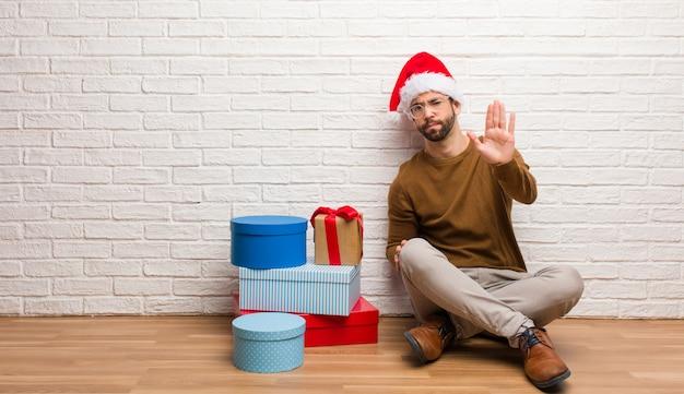 Junger mann, der mit den geschenken feiert weihnachten feiert hand in front setzen sitzt