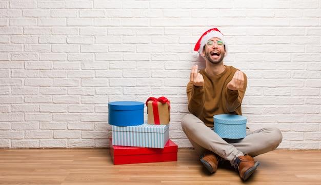 Junger mann, der mit den geschenken feiert weihnachten sitzt, eine geste des bedarfs tuend