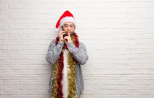 Junger mann, der mit den geschenken sitzt, die weihnachten feiern ein geheimnis halten oder um ruhe bitten