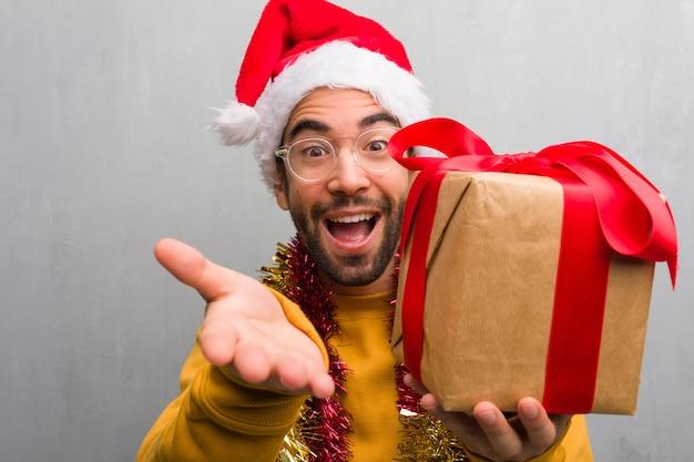 Junger mann, der mit den geschenken sitzt, die weihnachten feiern, heraus erreichen, um jemand zu grüßen
