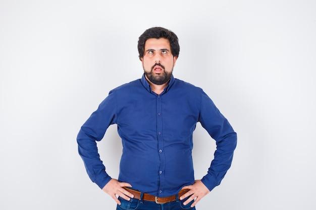 Junger mann, der mit den händen auf der taille steht, die augen im königsblauen hemd zusammenkneift, vorderansicht.