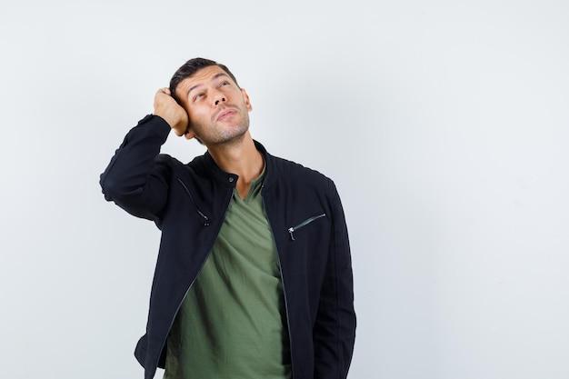 Junger mann, der mit der hand auf dem kopf im t-shirt, in der jacke nach oben schaut und verträumt aussieht, vorderansicht.