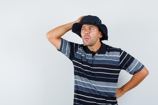 Junger mann, der mit der hand auf dem kopf in t-shirt, hut wegschaut und nachdenklich schaut, rückansicht.