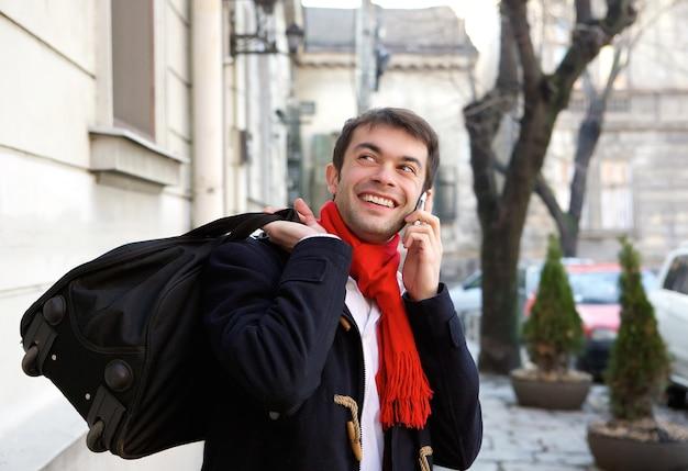 Junger mann, der mit der tasche ruft durch handy reist
