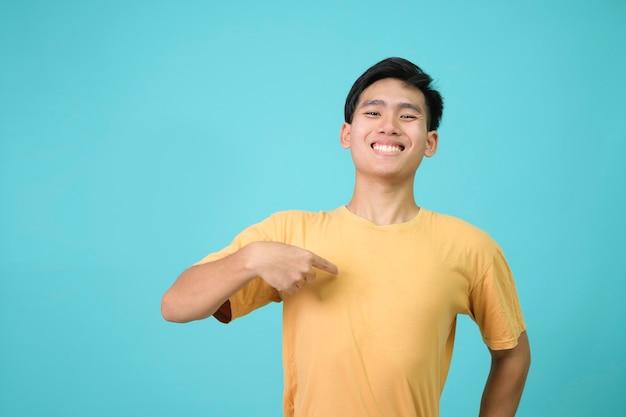 Junger mann, der mit einem lächeln im gesicht selbstbewusst aussieht und sich mit den fingern stolz und glücklich zeigt.