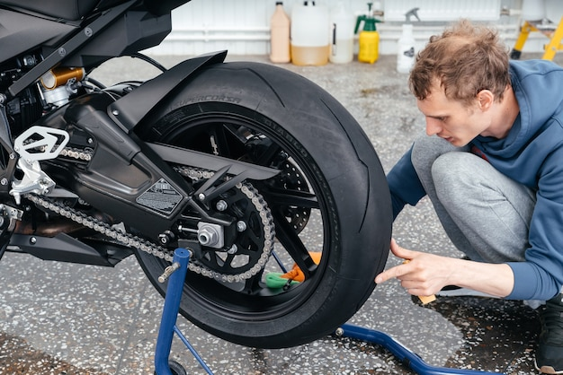 Junger mann, der mit einem modernen, leistungsstarken motorrad von bmw black sportbike säubert oder arbeitet