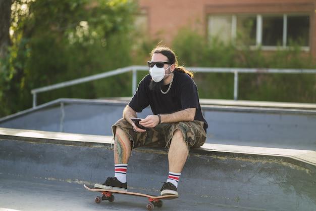 Junger mann, der mit einem skateboard im park sitzt und eine medizinische gesichtsmaske trägt - covid-19-konzept