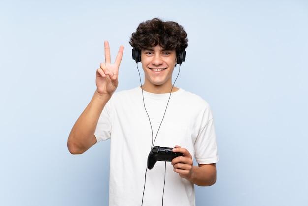 Junger mann, der mit einem videospielcontroller über lokalisierter blauer wand lächelt und siegeszeichen zeigt spielt
