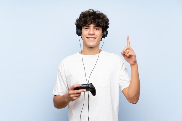 Junger mann, der mit einem videospielcontroller über lokalisierter blauer wand oben zeigt eine großartige idee spielt