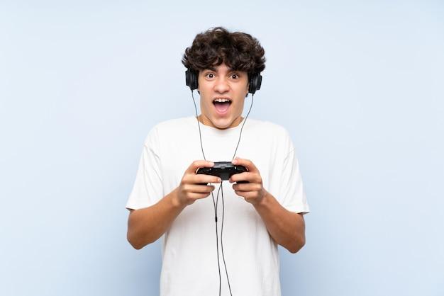 Junger mann, der mit einem videospielcontroller über lokalisierter blauer wand spielt