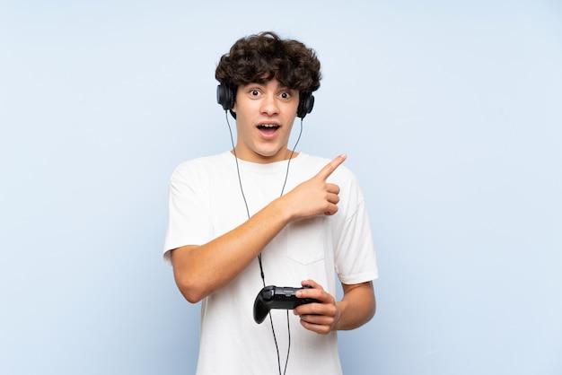 Junger mann, der mit einem videospielcontroller über lokalisierter blauer wand überrascht spielt und seite zeigt